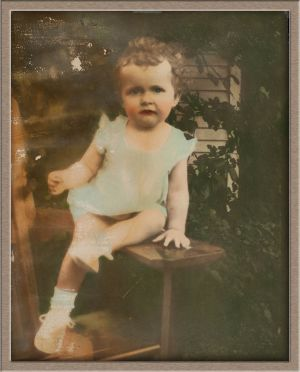 Before Moderate Digital Photo Restoration of Hand-Colored Outdoor Baby Portrait